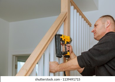 Installation nailing the railing for stairs with an air gun wooden railing