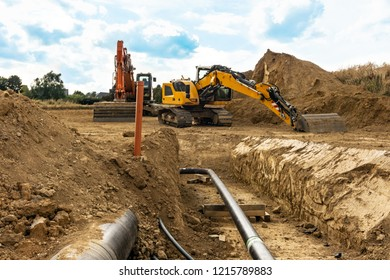 Installation of new gas pipes on a building site with a view down the open trench and heavy duty machinery and digger in the background