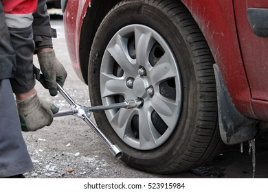 installation of passenger car wheel and replacement on winter tire in winter cloudy day outdoors