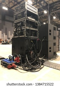 Installation of professional sound equipment for a concert. Racks with amplifiers, subwoofer speakers and electric power distribution boxes with signal cabels.