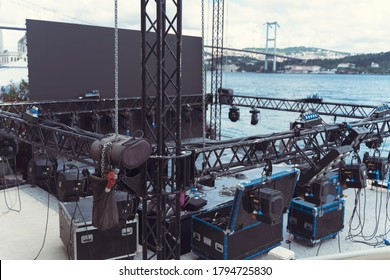 Installation of professional sound, light, led panel, video and stage equipment for a concert. Stage lighting equipment is clamped on a truss for lifting. Flight cases with cables.
