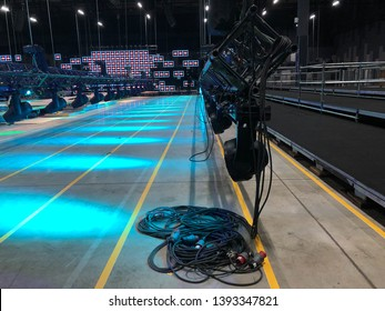 Installation of professional sound, light, video and stage equipment for a concert. Stage lighting equipment with power cables is clamped on a truss for lifting on led screen background.