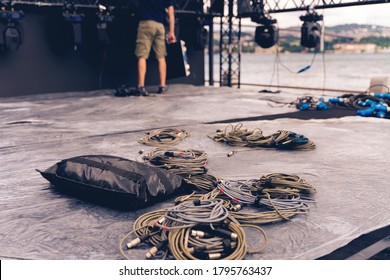 Installation of professional sound, light, video and stage equipment for a concert. Stage lighting equipment is clamped on a truss for lifting. Flight cases with cables.