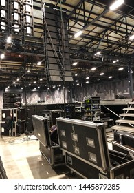 Installation of professional sound speakers, line array and stage equipment for a concert. Backstage area and tech zone with flight cases.