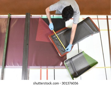 Installation of real carbon fiber: worker manually realizes a component in carbon fiber for automotive use. Measuring and preparation of a canvas made of real carbon  fiber. View from above.