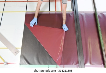 Installation of real carbon fiber: worker manually realizes a component in carbon fiber for automotive use. Preparation of a canvas made of real carbon fiber. View from above.