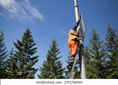 Installation road sign on pole. Road worker sets sign.
