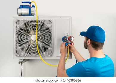 Installation service fix  repair maintenance of an air conditioner outdoor unit, by cryogenist technican worker evacuate the system with vacuum pump and manifold gauges in blue shirt and baseball cap