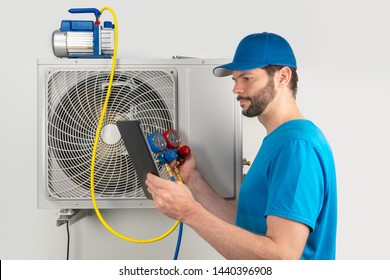 Installation service repair maintenance of an air conditioner outdoor unit, by cryogenist technican worker evacuate the system with vacuum pump manifold gauges tablet in blue shirt and baseball cap