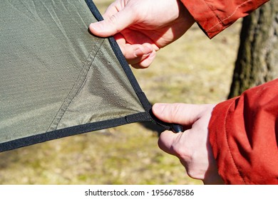installation set up of a tarp or tent made of rip-stop fabric. Close-up of male hands and the corner of an tarp with a grommet. Camping, travel, tourism concept