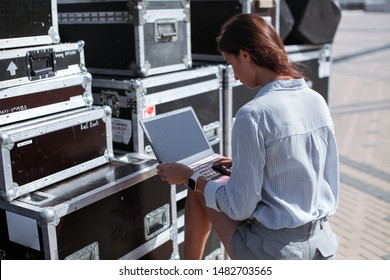 Installation of stage equipment and preparing for a live concert open air. Event manager portrait. Summer music city festival. Young serious woman stand and work with her laptop near the stage.