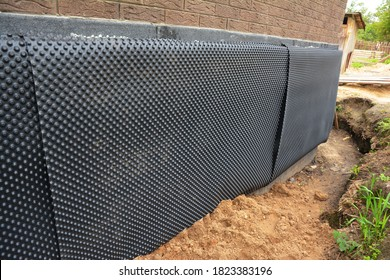 Installation of waterproofing dimpled membrane to insulate exterior basement or foundation wall of a brick house against moisture and water leakages.