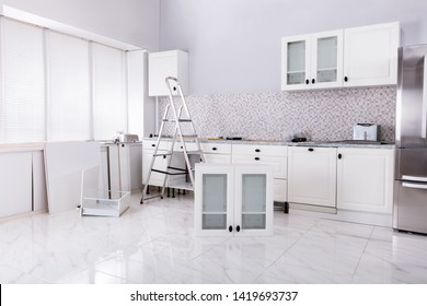 Installation Of White Cabinet With Tools And Ladder In The New Modular House