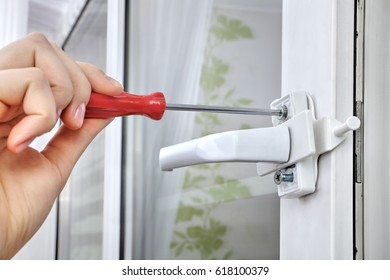 Installation of window restrictor to windows, using a screwdriver, close-up.