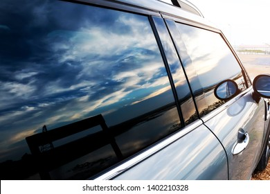 Installation of windshield protective film. Black light film on the car glass The windshield is attached to the side mirror and can see the reflection of the sea, the sunset sky.