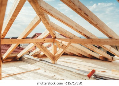 installation of wooden beams at house construction site. Building details with wood, timber and metal holders