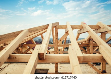 Installation of wooden beams and timber at construction site. Building the roof truss system structure of new residential house