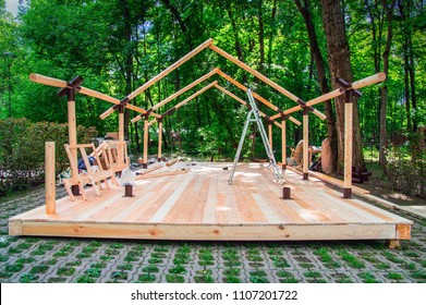 Installation wooden frame of a shopping pavilion under construction at the farmers market. New modern construction on a background of summer green dense forest. Wood Building frame assembly.