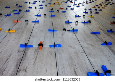 Installation of wood-style porcelain tiles on a floor. The colorful plastic spacers have the function of keeping the same distance between the tiles
