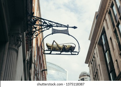 Installed in 1563 astonishing 1.5m golden grasshopper sign hanging high above outside 68 Lombard Street, London. Ancient lane curving east from Bank tube station