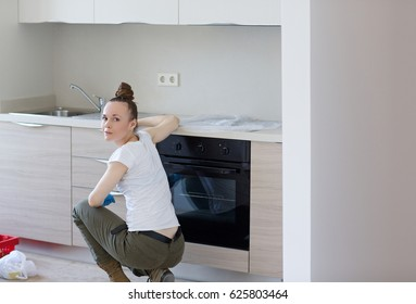Installed kitchen in a new apartment and  young housewife in front.