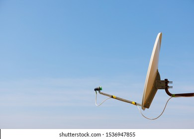 Installed satellite dish antenna or DTH for home TV over blue sky background with copy space