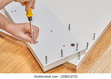 Installer hands assemble a piece of furniture, he fit together two chipboard using screwdriver and cam lock screw.