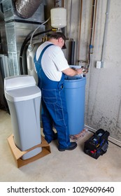 Installer inputting the settings on a new replacement water softener that he has just installed in a basement utility room