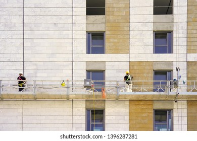 Installers in the construction cradle repair the facade of a house. Workers on a lift work on a construction of a multistory house. Construction workers on scaffold