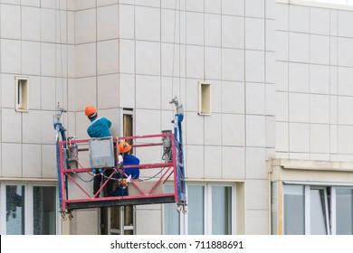 Installers in the construction cradle repair the facade of a house.