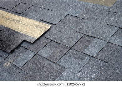 Installing asphalt roofing shingles. Installation of waterproofing coating in construction.