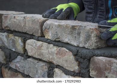 Installing brick, build a brick wall. Bricklaying foundation walls, lay bricks.