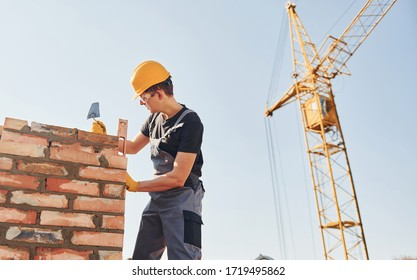 Installing brick wall. Construction worker in uniform and safety equipment have job on building.