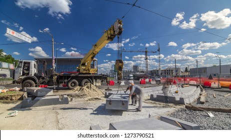 Installing concrete plates by crane at road construction site timelapse. Industrial workers with hardhats and uniform. Reconstruction of tram tracks in the city street