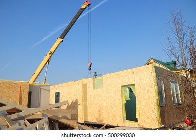 Installing Frame House Structural Insulated Panel - SIP with Crane Hook.  Structural Insulated Panels (SIPS) technology is the building technology of the future. Building SIP House Construction.