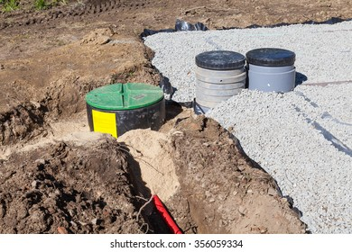 Installing a gravel and sand filter bed for a domestic septic tank showing the electric wiring , pump, trimmed plastic liner and filtration pipes  for effluent and sewage disposal