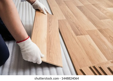 Installing laminated floor, detail on man hands with white gloves fitting wooden tile, over white foam base layer