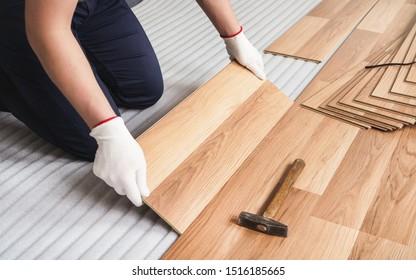 Installing laminated floor, detail on man hands in white gloves, holding wooden tile, over white foam base layer, small hammer near