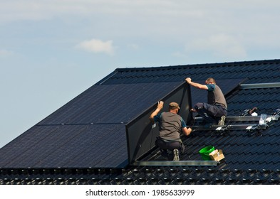 Installing new black solar panels on the metal roof of a private house. Ecology, renewable energy and green sustainable source of power abstract.
