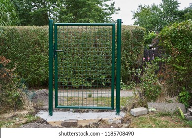 Installing a new green mesh metal garden gate and fence around the perimeter of the property with dug up concrete and stone in the foreground