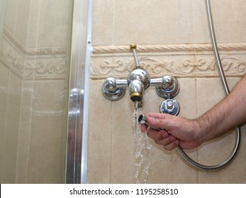 Installing a new hose on an used shower mixer tap in a shower cabin