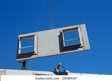 Installing precast concrete wall panel with crane and two workers in the construction site