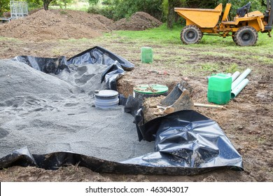 Installing the sand  and gravel filter bed on a domestic septic tank showing the black plastic  liner,  filtration unit  and pump  with a small front end loader  behind  for household sanitation