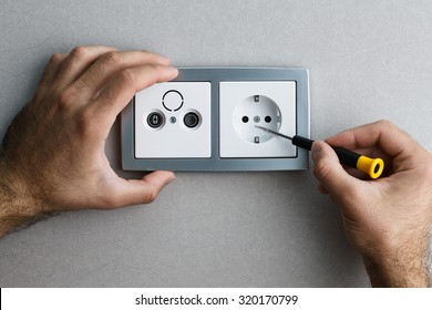Installing a silver wall-mounted AC power socket with a screwdriver on a grey wall, renovating home. Close up view.