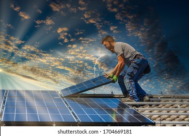 Installing solar photovoltaic panel system. Solar panel technician installing solar panels on roof. Alternative energy ecological concept.