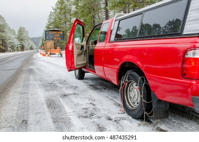 Installing tire chains on a truck on winter road