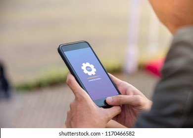 Installing update concept on phone screen. Man holding phone doing installing update process with gearbox percentage progress and loading bar.