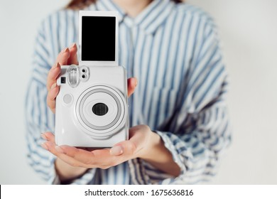 instant camera. girl holds photo frames and a white camera.Modern camera, photo white wooden background.