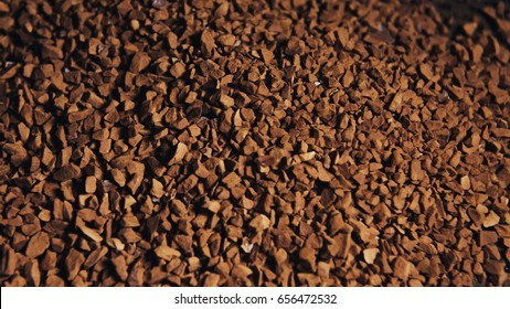 Instant coffee granules scattered brown closeup.