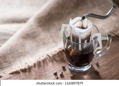 Instant drip coffee using paper type filter with beans on wooden background
